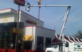 man in bucket truck over Mcdonalds
